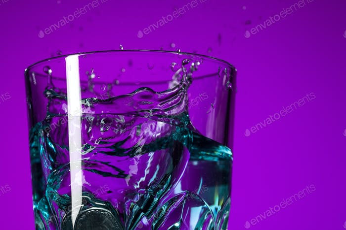 The water splashing in glass on lilac background