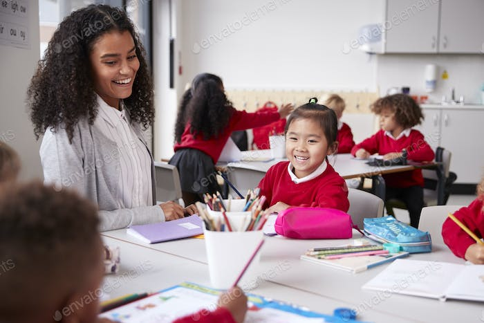 Female teacher and Chinese schoolgirl sitting at a table in an infant school class smiling