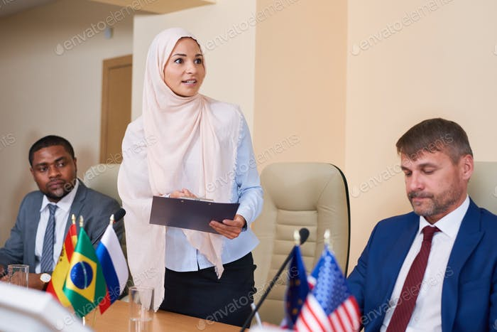 Young muslim female in hijab making report at conference