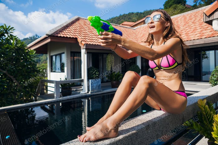 pretty slim woman playing with watergun toy at pool on summer tropical vacation