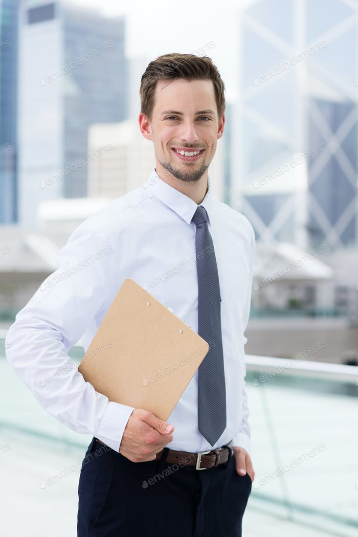 Businessman holding with clipboard at outdoor