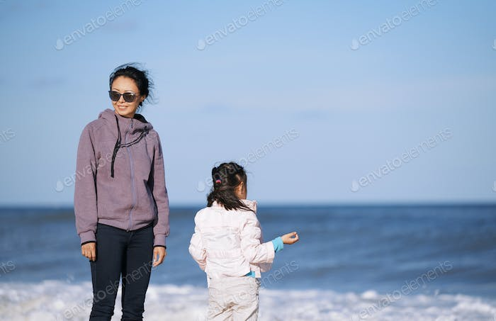 Happy mother and daughter having fun next to the ocean