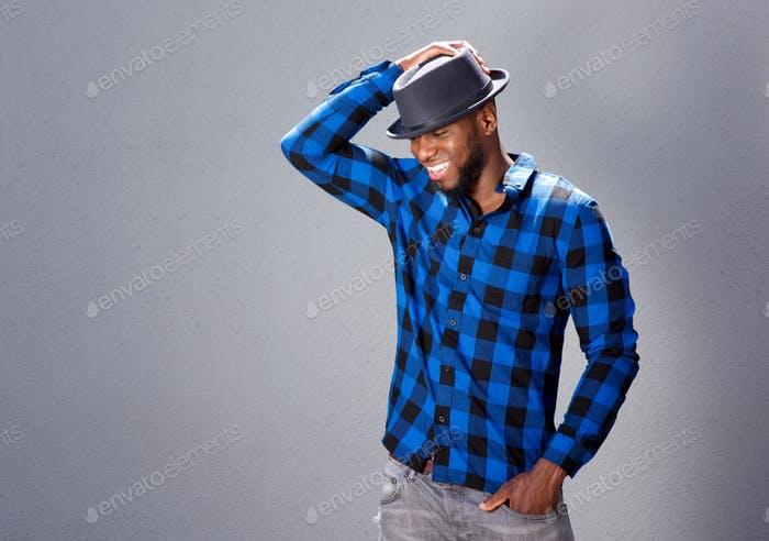 happy handsome man laughing with hand to hat