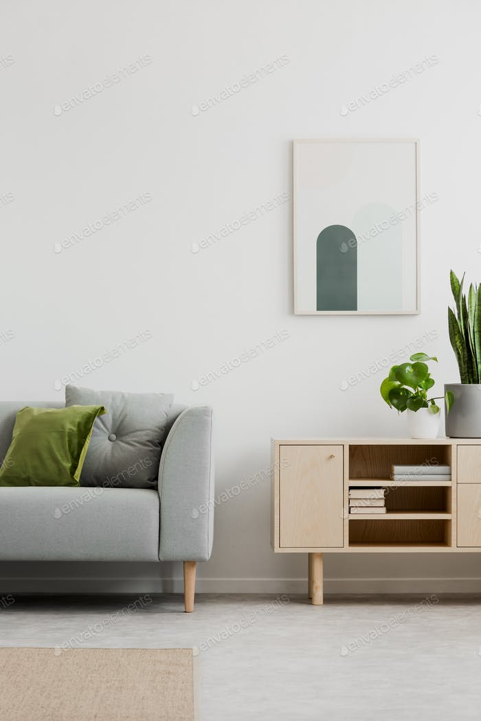 Poster above cupboard in simple living room interior with grey s