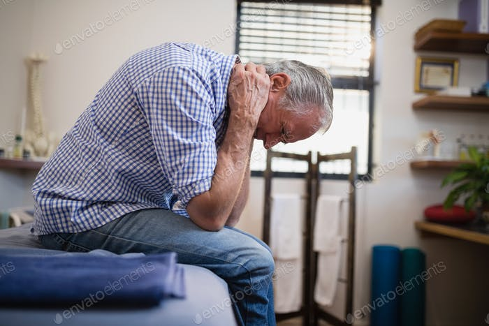 Side view of senior man sitting with neck pain on bed