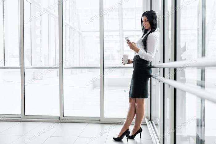 Erfolgreiche Geschäftsfrau mit Kaffee und Smartphone im Büro