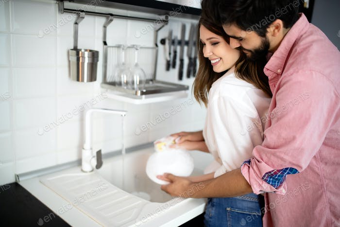 Young couple doing dishes in the kitchen while hugging and having fun