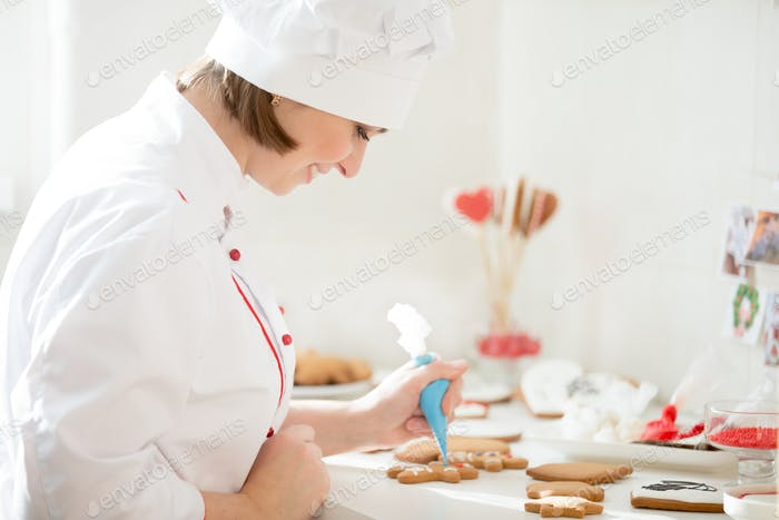 Professional smiling confectioner decorating a gingerman