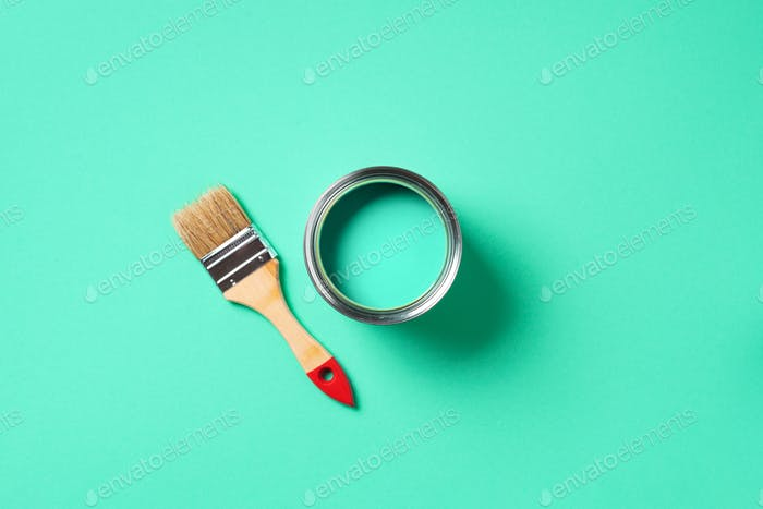 Paint brush and open paint can with on trendy green background. Top view, copy space. Appartment