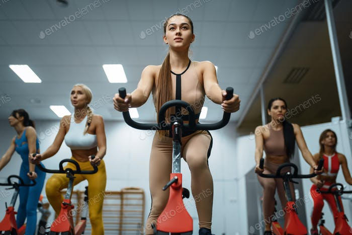 Women on stationary bikes, front bottom view