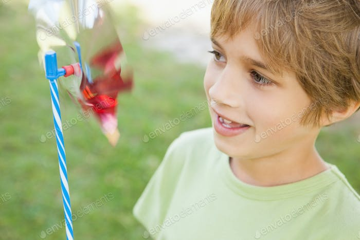 Smiling young boy looking at pinwheel in the park