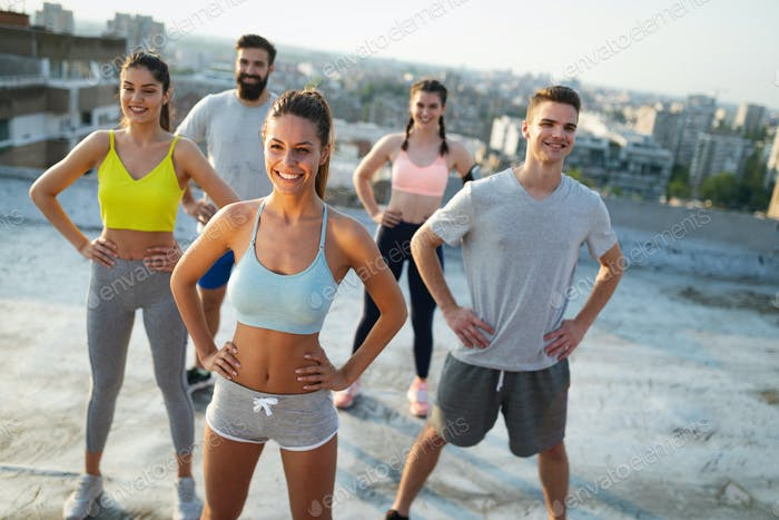 Group of young happy people friends exercising outdoors at sunset