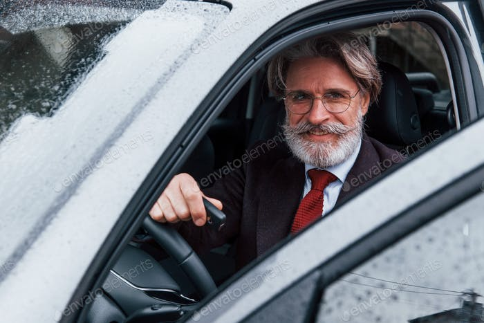Happy stylish senior man with grey hair and mustache is in the modern car