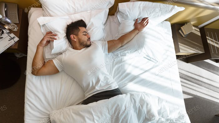 Young man sleeping in bed, staying in hotel