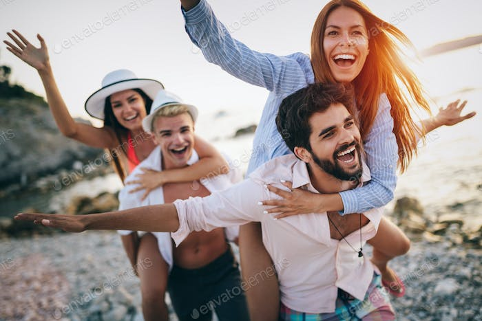 Cheerful friends enjoying weekend and having fun on beach