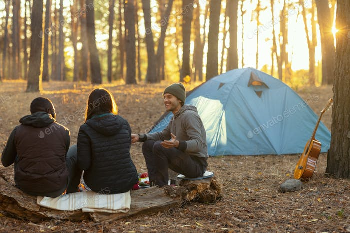 Back view of friends camping in autumn forest