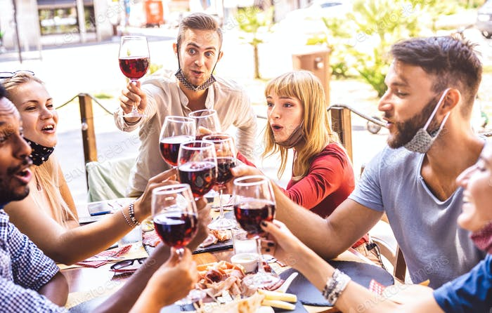 Friends toasting red wine at restaurant bar with face masks