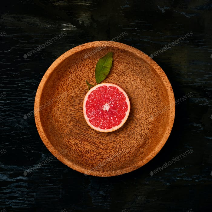 Grapefruit citrus fruit halves on wooden plate