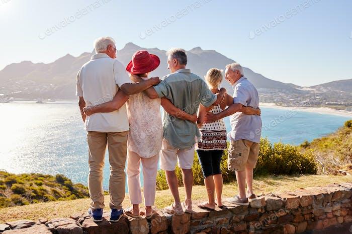 Vista trasera de los Amigos mayores que visitan el punto de referencia turístico en las vacaciones de Grupo de pie en la pared