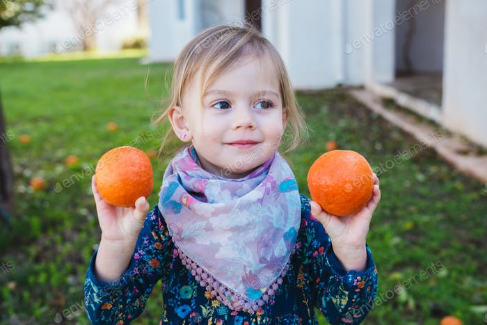 Little girl holding oranges in the garden