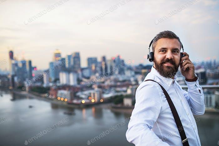 Ein Geschäftsmann mit Kopfhörern, die gegen London Blick Panorama stehen. Kopierraum.