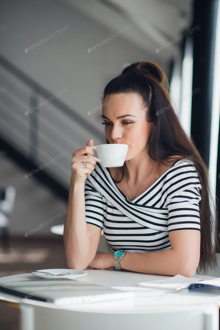 Beautiful young woman holding a cup of coffee looking away and smiling. Cheerful female enjoying a