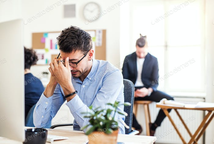 Young frustrated businessman with smartphone working in a modern office.