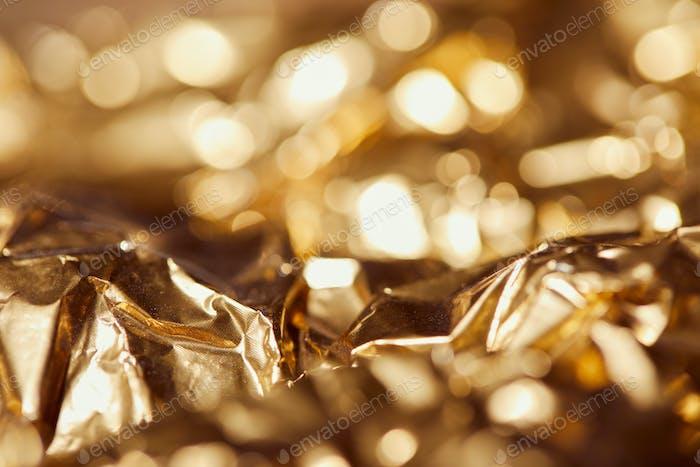 selrctive focus of golden foil with bright sparkling lights