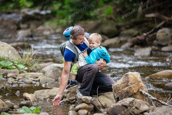 Caucasian man touching water in mountainous river while carrying his son in wrap sling