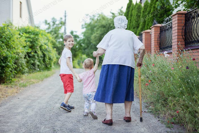 Young boy, little girl and their great   grandmother walking  down street