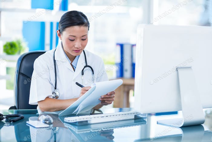 Concentrated doctor writing on clipboard in medical office