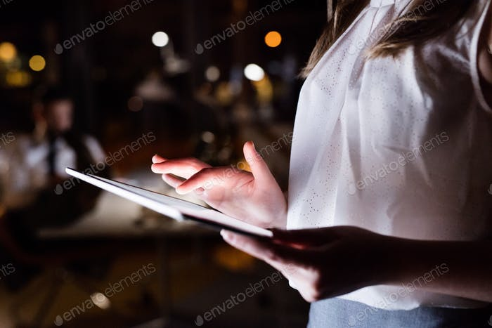 Unrecognizable businesswoman with tablet working late.