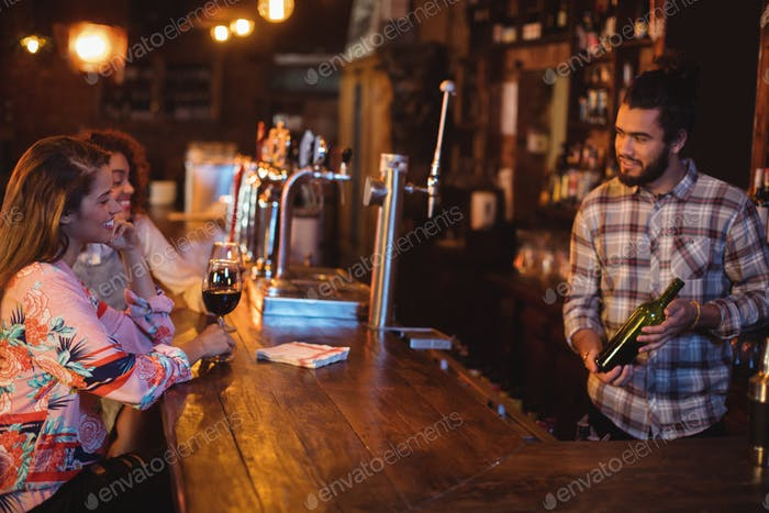Bartender showing wine bottle to women at counter