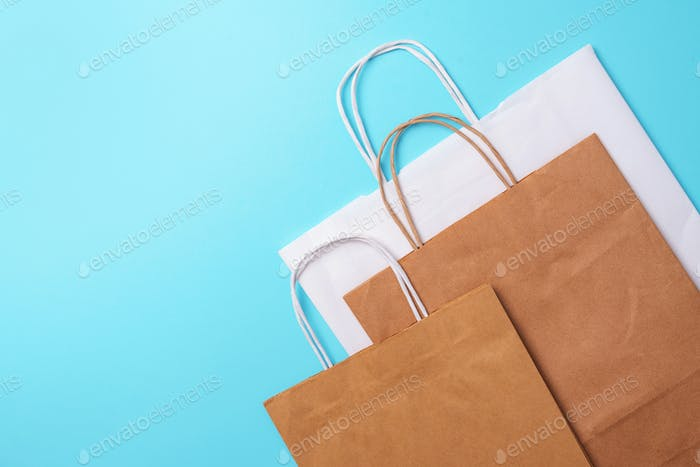 Craft paper cups, food box, gloves, bags, mask on blue background. Top view. Banner, copy space