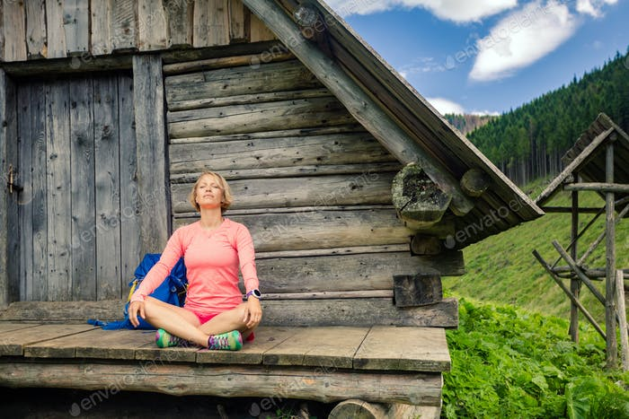 Woman relaxing and camping in inspiring mountain landscape