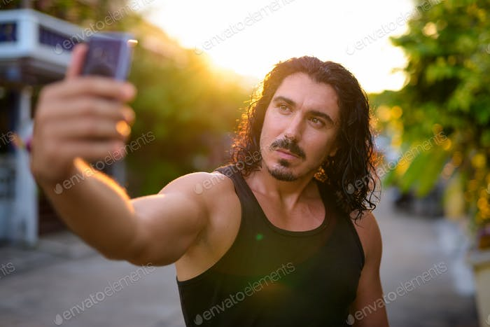 Handsome man with curly hair and mustache in the streets outdoor