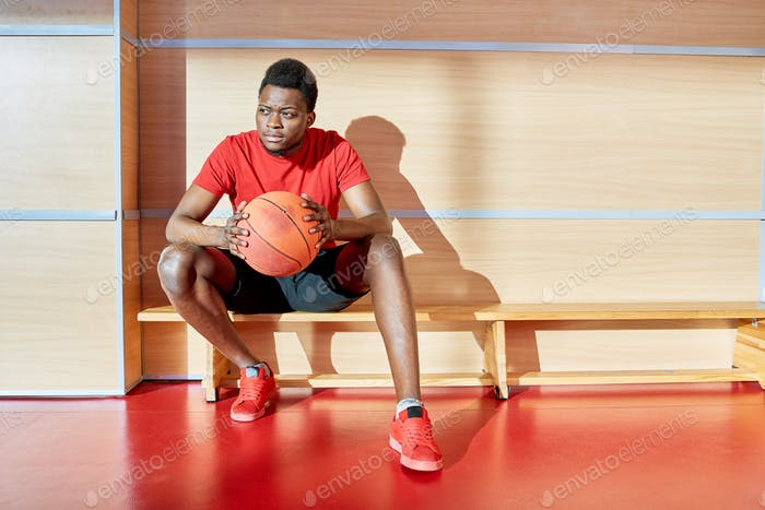 Black athlete with basketball ball on bench