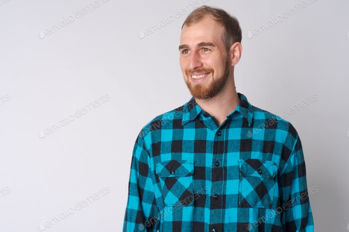 Face of happy young bearded hipster man thinking