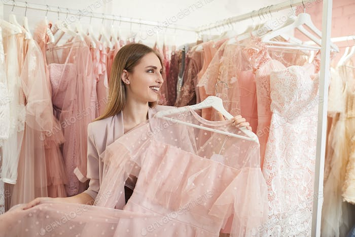 Smiling Woman Choosing Dress in Boutique