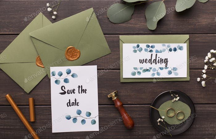 Preparing wedding invitations and folding envelopes on wood