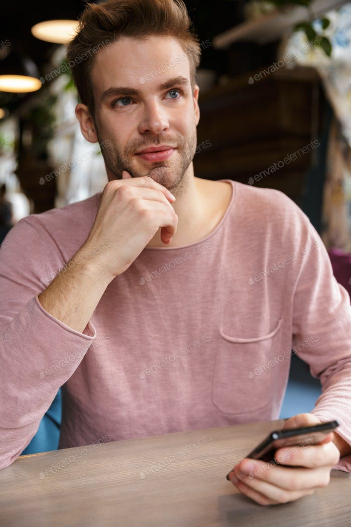 Attractive young man using mobile phone