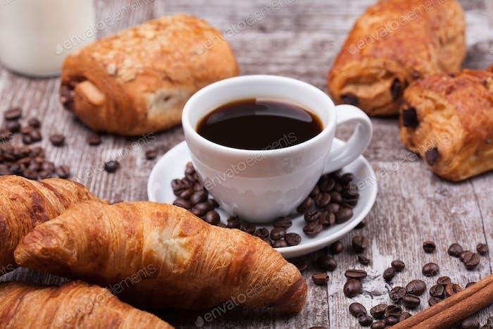 Tasse Kaffee mit Gebäck auf rustikalem Holztischhintergrund