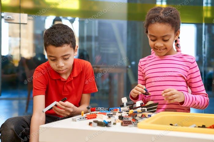 Afrikanische Mädchen und Jungen erstellen Spielzeug