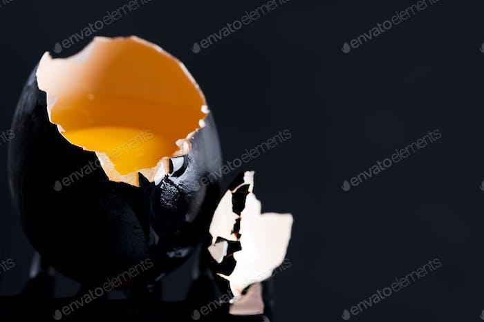 Schwarzes Ei mit Eigelb und Tropfen am Rand eines schwarzen Hintergrunds