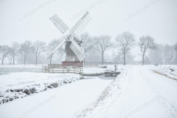 Dutch windmill in snowfall during winter