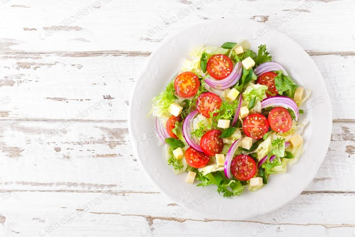 Fresh vegetable salad with tomatoes, lettuce, onion and cheese on white wooden background