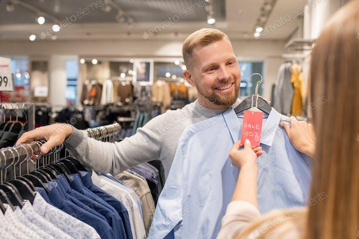 Joven feliz mostrando su novia camisa azul con cincuenta por ciento de descuento