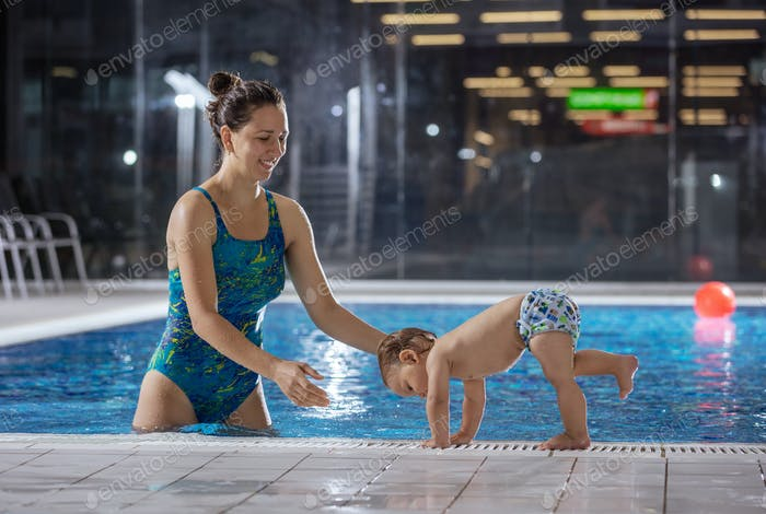 Young woman playing with little son by poolside