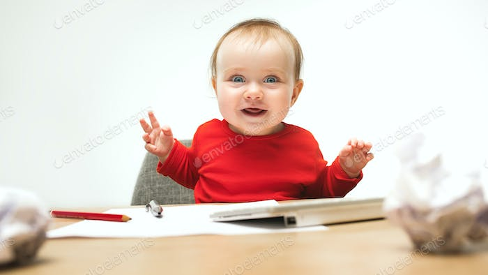 Happy child baby girl toddler sitting with keyboard of computer isolated on a white background