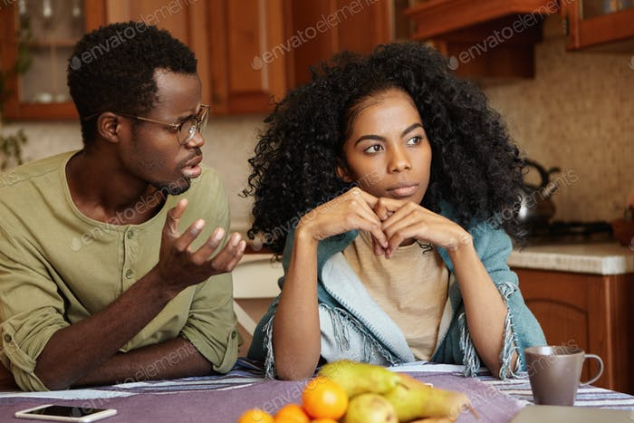 Why did you do this to me? Indignant depressed young Afro-American male in glasses trying to have co